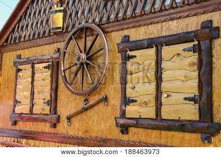 Old style wooden cottage with decorative wheel between shuttered windows