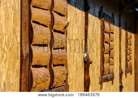 Wall of old style wooden cottage with decorative shuttered windows