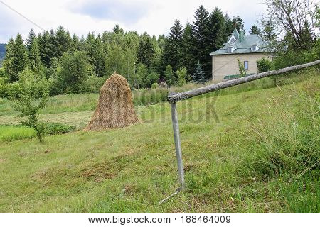 Haystack on green lawn near modern house on forested hill