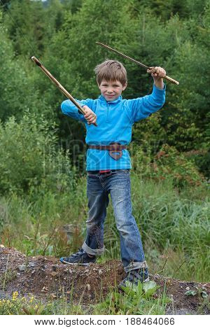 Boy with wooden sword in summer forest park