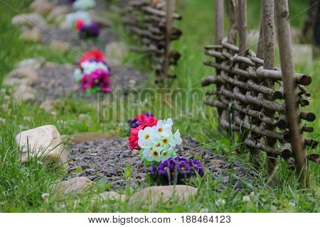 Original colorful flowerbed with decorative wooden fence