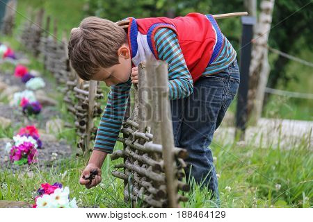 Boy with wooden sword near original flowerbed with decorative fence
