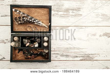 Wooden box with wedding rings bird's paws feathers empty bottles and stones on wooden background free space. Wedding decorations