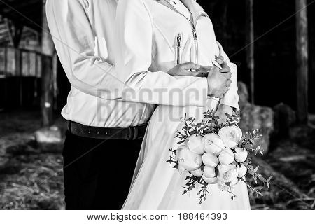 Groom embracing the bride with bouquet of peony in stable. Wedding couple in love at wedding day