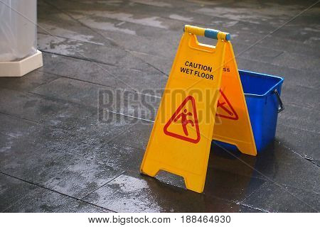 Yellow Caution wet floor sign on wet floor with blue bucket