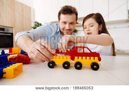 Precious moments together. Young single father and his little daughter spending quality time together via constructing a car model with the help of a construction set