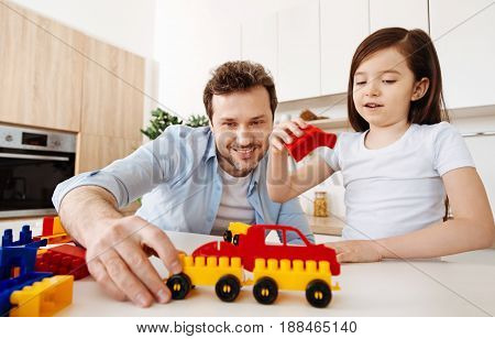 Quality time. Pleasant young man enjoying himself while assembling a car from the construction set with his smiling daughter holding a red part in her right hand