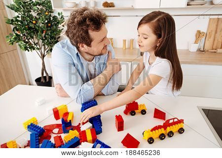 Father-daughter communication. Young curly father and his pretty little daughter sitting near the working surface full of the colourful construction set parts