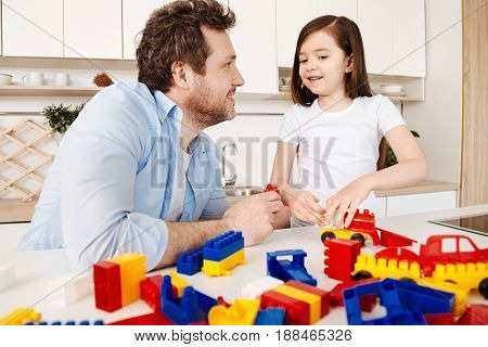 Lovely day together. Young bristled man smiling at his daughter and holding a red construction set part while she trying to assemble a car model staying near the surface full of toy pieces