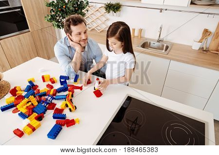 Fond look. Young cheerful father sitting in the kitchen, resting his face on palm and looking at his daughter with great love while she making a car model with the colourful construction set