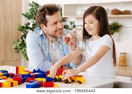 Sincere emotions. Pleasant cheerful father and his joyful little daughter looking happy and smiling broadly while the girl assembling a car model with a constructor set and the man pointing at it