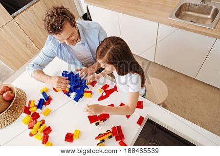 In full swing. Upbeat smiling father and his little daughter being totally engaged in playing together, assembling construction set and gathering a pile of blue parts near the man