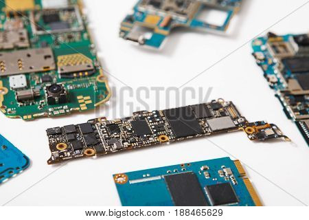 Digital gadgets components, repair shop concept. Motherboards of disassembled smartphones on service center workplace.