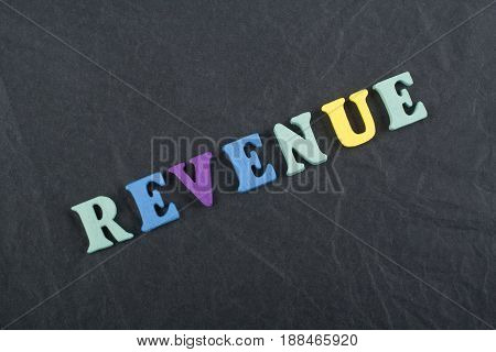 REVENUE word on black board background composed from colorful abc alphabet block wooden letters, copy space for ad text. Learning english concept