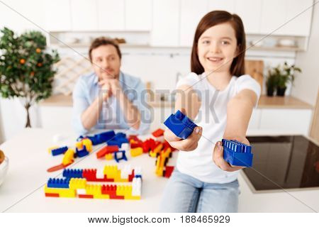 Here you go. Cheerful little girl sitting on the top of the counter and holding out two blue construction set pieces being in the focus while her dad resting his chin on the hands in the background