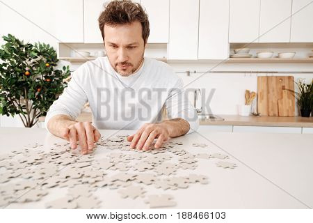 Brain game. Handsome young man in a white jumper sitting in the kitchen at a white counter and piecing together a jigsaw puzzle with an orange tree in the background