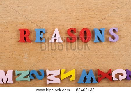 REASONS word on wooden background composed from colorful abc alphabet block wooden letters, copy space for ad text. Learning english concept