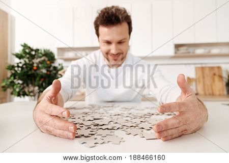 It is mine. The focus being on the neat hands of a handsome young man sitting at a kitchen counter and  moving jigsaw puzzle pieces closer to him