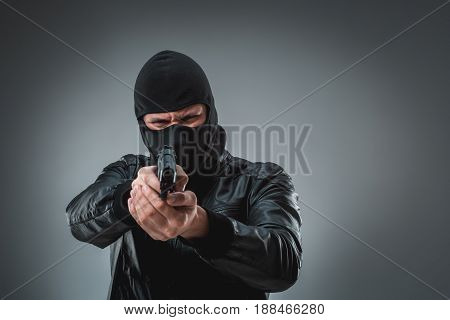 Burglar or terrorist in black mask shooting with gun. A man in the studio on a black-and-gray background