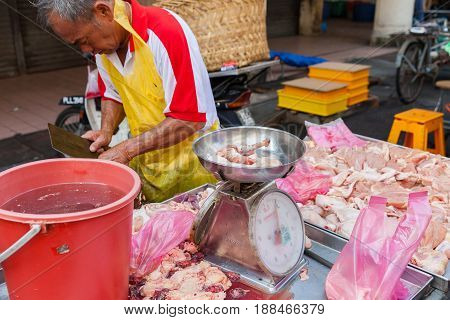 GEORGE TOWN MALAYSIA - MARCH 23: Butcher sells chicken meat at the wet market of George Town Penang Malaysia. on March 23 2016 in George Town Malaysia.