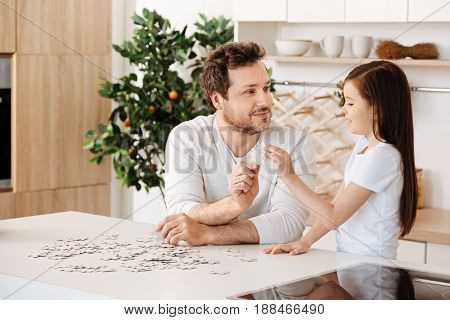 Happy together. Loving single father and his cute little daughter sitting at the kitchen counter, looking happy and each holding a jigsaw puzzle piece and joining them thus showing their unity