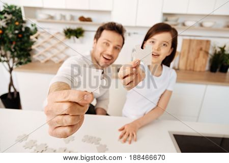 We love puzzles. The focus being on the hands of a cheerful young father and his smiling daughter looking upbeat and holding out jigsaw puzzle pieces to the camera.