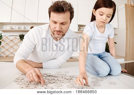 Captivated by puzzles. Delicate pretty girl sitting on her knees on the kitchen counter and doing a jigsaw puzzle together with her father, both being fully immersed in the process