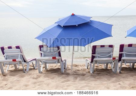 Empty deck chairs and umbrella on the beach.