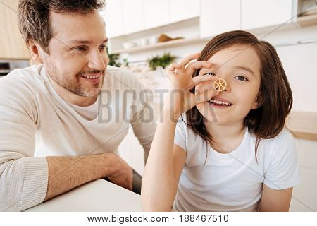 Fooling around. Cheerful cute girl goofing around by pressing a piece of wagon-wheel pasta to her nose while her father looking at her with a broad sincere smile