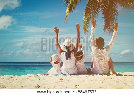happy family with two kids hands up on tropical beach