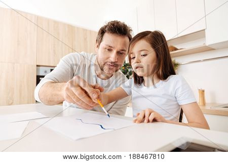 Bonding while painting. Pleasant young father sitting next to his little daughter and holding her hand with a brush, helping her in painting a line with blue watercolours