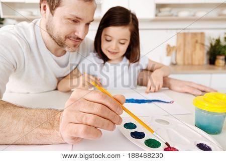 Painting together. Beautiful young father holding a brush and picking a red watercolor from a palette while hugging his beloved little daughter painting a picture