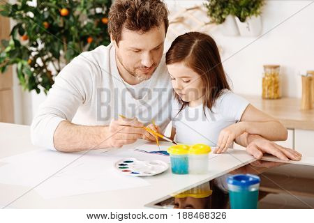 Treasured moments. Inspired loving single-parent family enjoying themselves while painting together one picture with two brushes, sitting at the kitchen counter with a palette and a water container