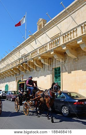 VALLETTA, MALTA - MARCH 30, 2017 - Horse drawn carriage passing the Holy Infirmary along Triq Il-Mediterran Valletta Malta Europe, March 30, 2017.