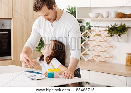 Sweet bonding. Gentle caring father standing behind his little daughter, holding her hand with a brush and looking at her face with a smile while the girl looking happily up at him