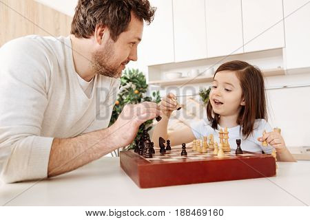 Excited about game. Handsome young father and his adorable little daughter looking happy and excited while holding chess pieces, ready to putting them on the chessboard
