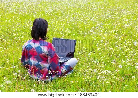 Colombian woman sits with laptop in meadow with blooming flowers