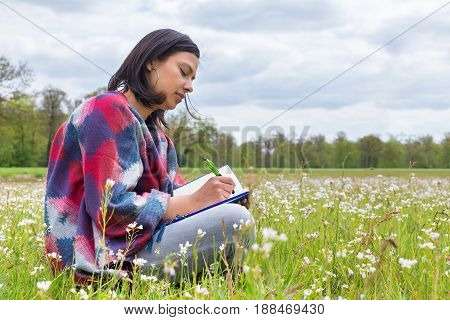 Colombian woman writes in pasture with spring flowers