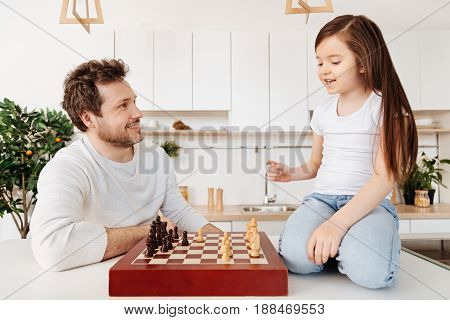 Beginning the game. Petite cheerful girl sitting on her knees on the kitchen counter and thinking over her next move while her father looking at her and smiling.