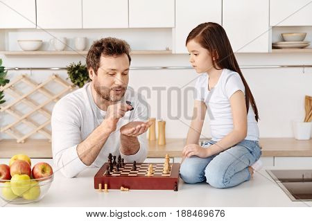 Complicated rules. Smart and wise father holding a knight piece in his hand and showing its movement while his daughter sitting on her knees near the chessboard and listening to him attentively