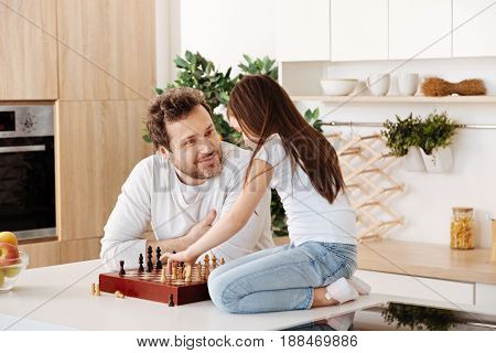 Full of admiration. Pleasant young father giving his daughter a gentle loving look and smiling at her while she moving a chess piece