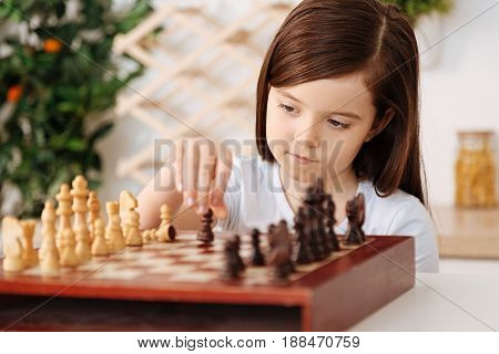 Playing herself. Smart little girl making a move with a pawn, playing alone and being involved in the process while her father being away