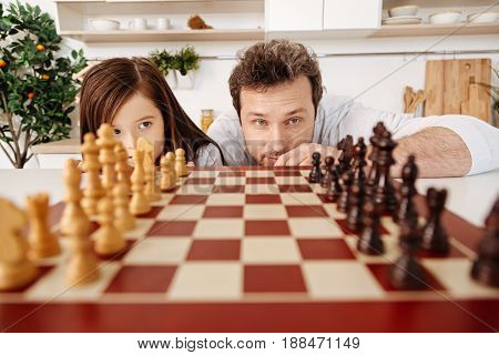 Order lovers. Pleasant young father and his beautiful little daughter looking at the chess pieces set up on the chessboard and checking whether they standing correctly