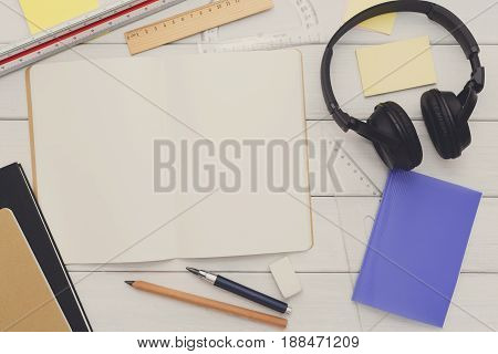 Education and work concept, top view shot of designer or architect workplace. Stationery supplies and headphones on white wooden desktop, flat lay, copy space, mockup