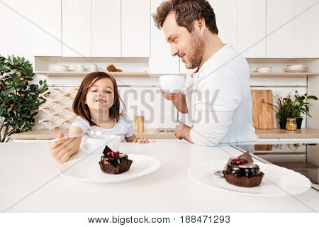 Pleased happy little girl holding a spoon in her hands and reaching out for cake while her father standing near her, smiling and drinking tea from a cup