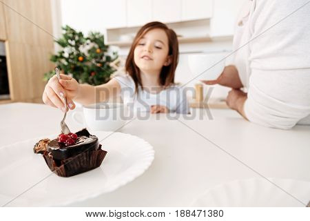 Delicious treat. Content little girl putting a teaspoon into a chocolate cake decorated with cherries while her father standing near her holding a cup of tea