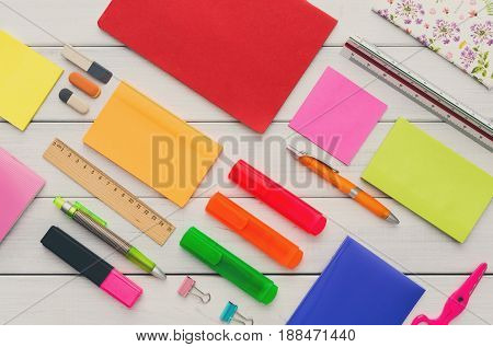 aset of colorful markers, sticky notes, notepads, pens, rulers and erasers on white wooden table background, top view, nobody, objects