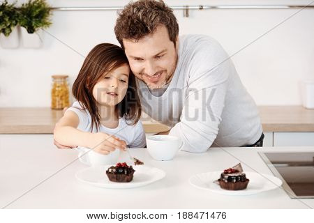Sweet pleasure. Pleasant caring father hugging his daughter and smiling while she being about to treat herself to some cake