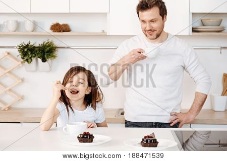 Pure delight. Blissful cute little girl relishing chocolate cake with her eyes closed and a happy smile while her father standing behind her and looking at her with a smile.