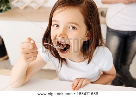 Enjoying dessert. Beautiful brown-haired girl enjoying a spoonful of cake and having some cream on her nose while her father standing in the background